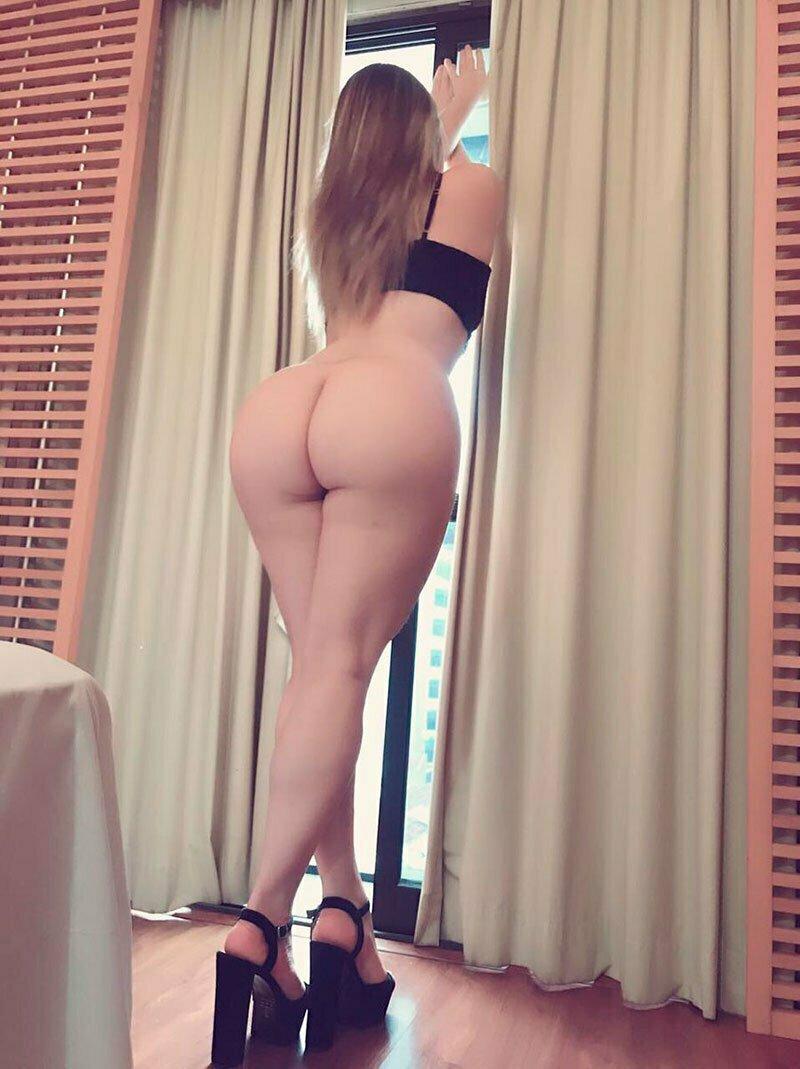 mulher gostosa nua em pé na janela
